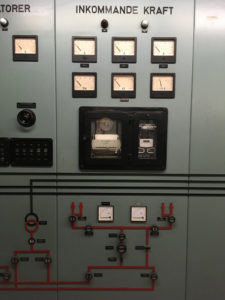 """Kontrollpanel i äldre stil. Olika mätare och knappar sitter på panelen. Över dem står """"Inkommande kraft""""."""